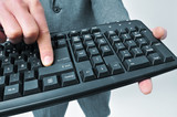 man in suit pressing the enter key of a keyboard