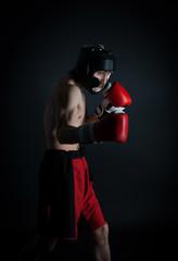 Man in helmet boxing in black background