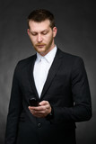 young business man looking at phone