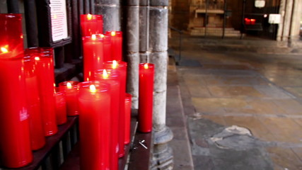 Pile of lighted red candles in church
