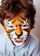 Little cute boy with faceart on birthday party, tiger close up