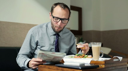 Businessman reading magazine during breakfast in hotel room