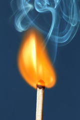 Lighted match on a blue background.