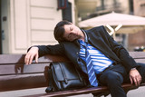 Businessman sleeping on the bench in the park feeling tired