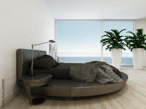 Black bed against huge window with sea / ocean view