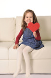 little girl on couch holding red heart cardboard cut