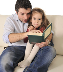 Father reading and telling fairy tale to little daughter