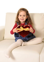 little girl sitting on couch holding red heart cardboard cut
