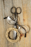 old scissors, glasses and hank of packthread on wooden backgroun