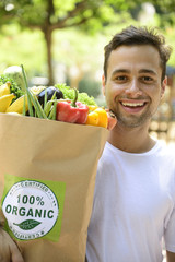 Happy man carrying a bag of organic food.