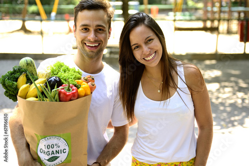 Happy couple carrying a bag of organic food.