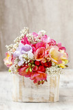 Bouquet of colorful freesia flowers in wooden shabby chic box.
