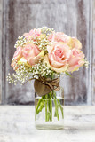 Bouquet of pink roses in transparent glass vase.