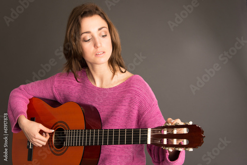 Young woman tuning acoustic guitar