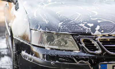 Part of car covered with soap foam