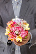 Man holding bouquet of colorful freesia flowers