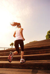 fitness young woman running up on wooden stairs