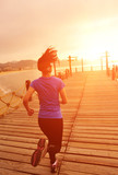 fitness  young woman running seaside wooden pier