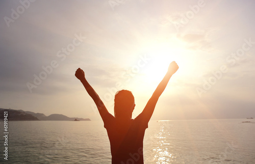 cheering woman open arms to sunrise seaside