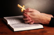 Hands holding wooden cross over open russian holy bible
