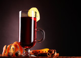 mulled wine in the glass, spice and lemon on purple background