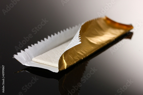 Chewing gum on the wrapping foil on gray background