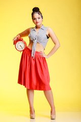 Full length fashionable pin-up girl sexy woman holding red clock
