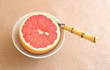Red grapefruit in bowl with spoon
