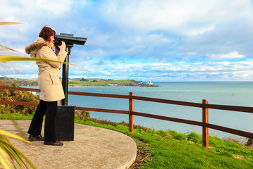 woman looking through sightseeing binoculars the ocean
