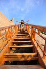 woman hiker climbing wooden stairs on mountain huashan peak