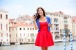 Travel tourist woman with camera in Venice, Italy