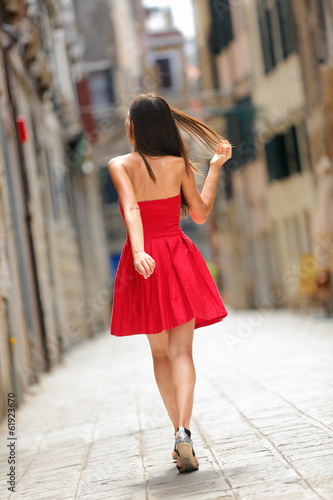 Woman in red dress walking in street in Venice