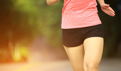 woman runner jogging at forest trail