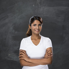 Happy Indian woman standing in front of a blank chalkboard.