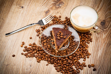 Cup of coffee latte and a cake on wooden table