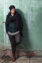 young fashion man leans on old wall