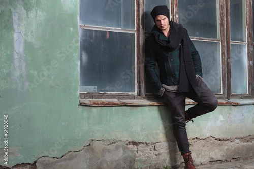 young fashion man leans on window sill