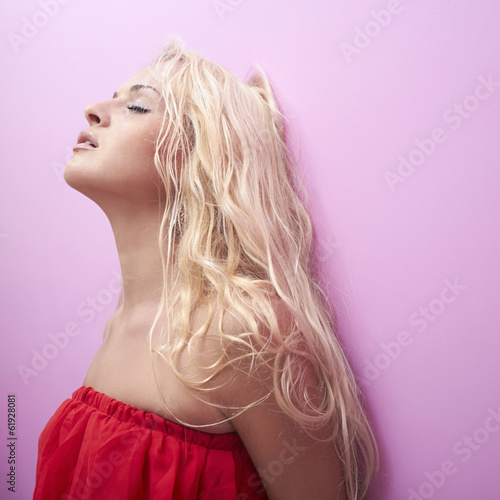 beautiful blond woman with closed eyes.sexy girl near pink wall