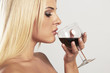 Beautiful blond woman tasting red wine