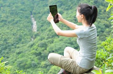 woman hiker muntain peak use digital tablet