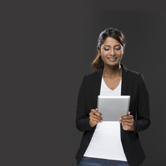 Happy Indian Woman using a digital tablet.
