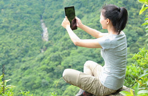 woman hiker muntain peak use digital tablet