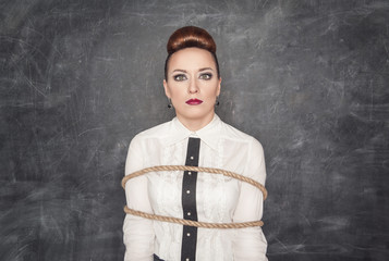 Scared business woman tied with rope