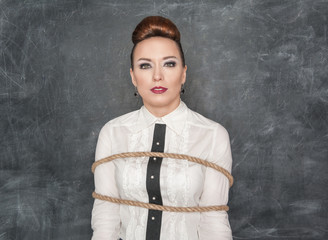 Business woman tied with rope