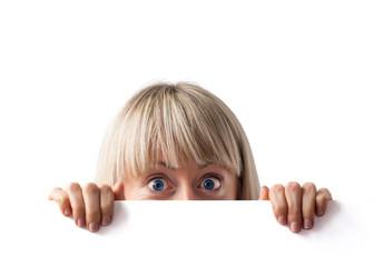 Surprised woman hiding behind blank whiteboard