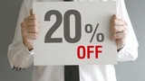Salesman holding sale tag with twenty percent sales discount