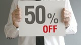 Salesman holding sale tag with fifty percent sales discount