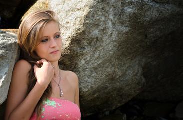 Pretty blue eyed, brunette girl in bikini against rocks