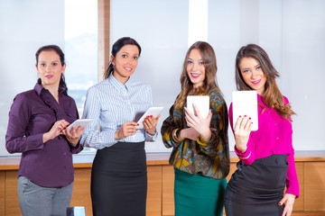 Four business woman with tablet computers