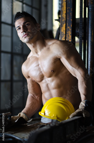 Attractive muscular manual worker shirtless with hardhat